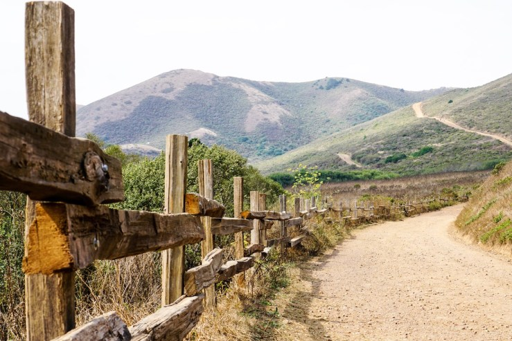 Picture of a hilly path with a wooden fence lining the side